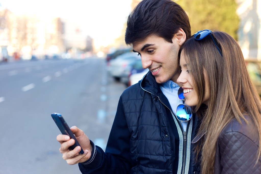 Portrait of young couple of tourist in town using mobile phone. ; Shutterstock ID 255421201; Purchase Order: 2018-1011; Job: MC Dan besplatnog parkiranja; Client/Licensee: Mastercard; Other:
